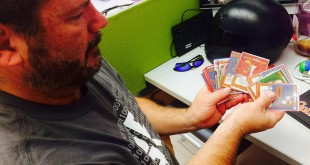 Chuck Call, the chief financial officer for Atheris Games, shows off some of the cards for his company's newly funded game while sitting in the Gator Hatchery. The game, Cul-De-Sac Conquest, fundraised $10,000 in 52 hours.