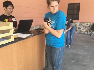 """Stacy Walker, 26, checks out with volunteer Amber Young Parker at the reception desk, which is just outside the clinic, with her newly rescued, six-week-old kitten, Autumn Tuesday morning. """"Everyone was so friendly and so welcoming,"""" she said. Photo credit/Grace Hudgins"""