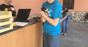"""Stacy Walker, 26, checks out with volunteer Amber Young Parker at the reception desk, which is just outside the clinic, with her newly rescued, six-week-old kitten, Autumn Tuesday morning. """"Everyone was so friendly and so welcoming,"""" she said."""