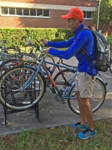 """Renee Gomez, UF senior, mounts his Gator Gears rental bicycle on the bike rack outside of Library West. 'They were really helpful,' Gomez said of the service Gator Gears delivers. 'They provide maintenance when you need it, where ever you're at.' Victoria Verdeja / WUFT"