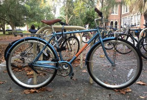 """""""One of the 100 Gator Gears rental bikes remains locked outside of Norman Hall while classes are in session. The bicycle was locked to a bike rack with the U-lock provided by Gator Gears, which is included in the rental fee."""""""