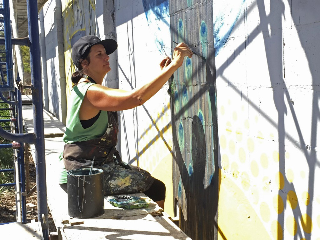 Wachter Martinez uses a peacock feather as a reference as she paints feathers onto the women's dress in the mural. She said she used peacock feathers in her this mural and previous work through the idea that peacocks are the ultimate beauty that nature can create.