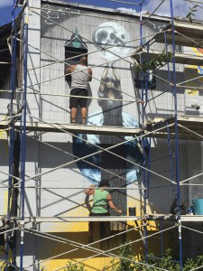 Carrie Wachter Martinez and her husband, Jesus, work on her mural for the 352Walls project on Thursday. The pair have only recently begun collaborating with each other with the murals on their building, Visionary Crossfit.