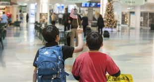 Two boys celebrate in the airport after officially entering the U.S. as registered refugees. The process of how refugees are screened for entry into the U.S. has generated new interest in the wake of the Syrian refugee crisis and the Paris terror attacks. Photo courtesy of Catholic Charities of Jacksonville.