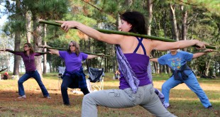 """Leela Robinson leads a """"Yoga for Gardeners"""" workshop, showing visitors how to do yoga with bamboo canes that mimic long handled garden tools. Photo by Mariana Riquezes /WUFT News."""