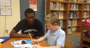 Devin Lawrence, a member of the Hawthorne High School basketball team, helps a first grade student, Jonas, with his reading. Students at Chester Shell Elementary School get extra reading help from Hawthorne High School athletes after school on Mondays through the Barbara Bush Foundation's Teen Trendsetters program. Photo Credit: Michelle Neeley/WUFT News