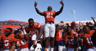 Florida running back Kelvin Taylor (21) stands on the wall in front of the student section while his teammates mingle with fans. (Greenberry Taylor/ WUFT News)