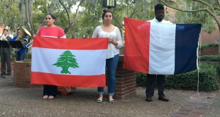 Students hold the flags of Lebanon and France during a vigil on Nov. 16, in remembrance of those who lost their lives in the recent terrorist attacks. Lebanese students expressed concerns that Facebook  only had safety notifications for those who had relatives and friends in Paris and not in Beirut and other places where attacks occurred. Photo by Ahmad Krecht, Vice President of the Lebanese American Society.