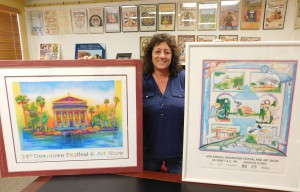 """Linda Piper poses with the poster for her last Downtown Festival & Arts Show as event coordinator and the one from 1995 in her earlier years as coordinator. """"I never expected that this would be my career,"""" she said. Photo Courtesy of Linda Piper."""
