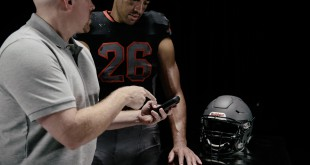 A coach demonstrates to a football player how to properly use the new sensor technology developed by Riddell for its football helmets. The technology works by placing special sensors inside the helmets with the data being sent to a monitoring device on the sidelines. The device then sends the data to a computer utilized by trainers and medical staff to monitor a player's vitals following a hard hit to the head. Photo provided by Riddell.