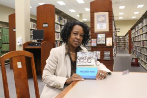 Co-author Cynthia Wilson-Graham holds her book at the Marion County Public Library. She did research for the book at Marion County Public Library and countless others, traveling as far as Atlanta. Marion County Public Library is located about four miles from the site of Paradise Park. Lindsay Alexander/ WUFT News
