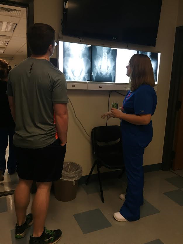 Christian Davis, a junior in the radiography program at Santa Fe College, discusses an x-ray of a human pelvis with Paul Whitlow, a sophomore nursing student who attended Santa Fe's radiography program open house Friday. Whitlow said before the open house, he didn't really know the difference between radiography and radiology. Shelby Davidson/ WUFT News