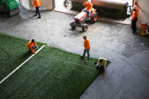 Workers install the synthetic turf in the football team's indoor practice facility. The synthetic turf is easier to maintain and may prevent injuries, but it may also come with the risk of containing trace contaminants and toxic chemicals. (Photo courtesy of Jason Kruse.)