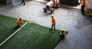 Workers install the synthetic turf in the football team's indoor practice facility. The synthetic turf is easier to maintain and may prevent injuries, but it also comes with the risk of containing contaminants and toxic chemicals. (Photo courtesy of Jason Kruse.)