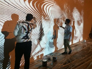 Artists, Andrews Antonaccio and Filio Glavez, of 2Alas projected their mural onto the side of the Hector Gallery so that they could trace and paint their work more easily. Photo by Sarah Kimbro/WUFT News.
