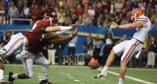 Alabama linebacker Keith Holcombe (42) extends his body to block Florida punter Johnny Townsend's (19) punt for a safety in the first half. (Greenberry Taylor/ WUFT News)