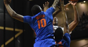 Florida defenders Dorian Finney-Smith (10) and Kevarrius Hayes (13) double team Vanderbilt's Damian Jones (30) as he goes up for a shot in the first half. (Greenberry Taylor/WUFT News)