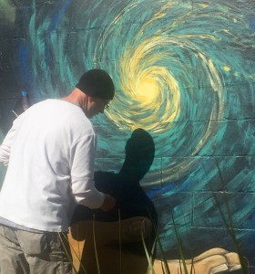 Local artist Tim Malles joined Jesus and Carrie Martinez on Monday to paint the mural's galaxy. Malles has been known for his astronomy-based art, and his work has been featured at the Florida Museum of Natural History. (Laura Gomez/WUFT News)