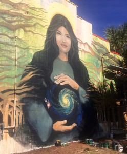 Local artists Jesus and Carrie Martinez are painting a mural on High Dive's Second Avenue wall on Monday. It is the wall's first mural since the '90s and part of the venue's effort to renovate. Local schoolteacher Stephanie Lee's face is featured on the wall. (Laura Gomez/WUFT News)