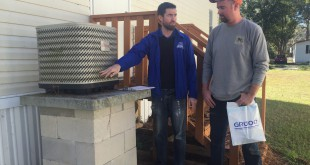 Michael McCabe (left) teaching Joshua Pettit (right) about ways to keep his air conditioning unit clean. He explains to Pettit that his unit is only five to six years old and should be fine. McCabe is also collecting information on the unit to make sure that it matches the air handler inside. (Sydney Martin/ WUFT News)
