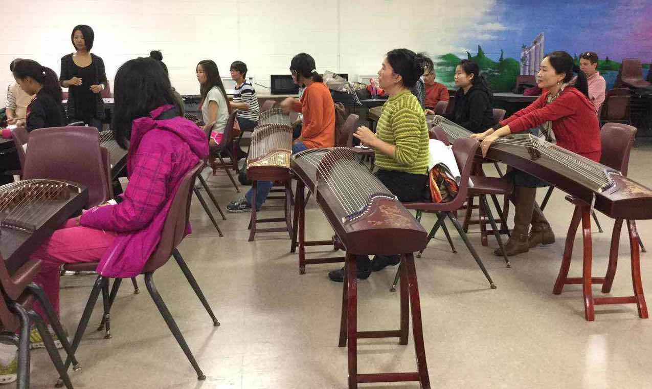 """Xiaodan Liang, gu zheng teacher at Hua-Gen Chinese School in Gainesville, teaches her students how to play the gu zheng in class. """"For me, teaching students is not about making money but promoting Chinese culture,"""" she said. Photo by Lanqiu Huang"""