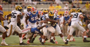 A swarm of Florida defenders try and bring down Michigan full back Sione Houma (39) in the second half. (Greenberry Taylor/WUFT News)