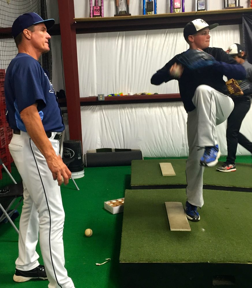 Jim Hickey coaches the pitching technique of Colton Avara, 12, who plays for Elite Babeball. (Kiara Beard/WUFT News)