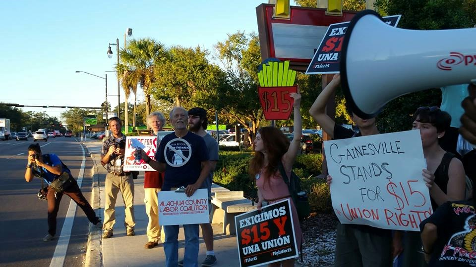 """Members of the Alachua County Labor Coalition and Gainesville residents demonstrate outside McDonald's as part of the """"Fight for $15"""" campaign to raise the minimum wage to $15 an hour. Photo courtesy of Mary Bahr."""