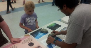 Riley, a Glen Springs kindergartner, matches up different types of rocks and minerals with photos. Harshit Saini, a UF geology student, taught Riley and many other Glen Springs students about where different types of minerals and rocks can be found. (Photo by Richard Whitely/WUFT)