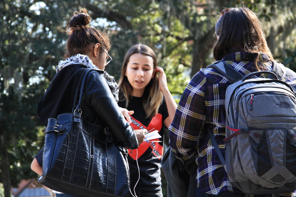 Ana Oliveira-Beuses, center, informs students about the University of Florida's Gators Against Human Trafficking at the Plaza of the Americas Monday. Oliveira-Beuses, historian, said the biggest obstacle to combating human trafficking is a lack of community education on the topic.
