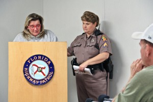 "Sgt. Tracy Hisler-Pace, right, opens the ""Hit and Run, Bad 2 Worse"" press conference Monday at 10 a.m. ""They really need to think about what they're doing,"" FHP spokesperson Hisler-Pace said, addressing people who have run from the scene of a crash. Renee Bryant, left, lost her son in 2014. She came to the Gainesville Florida Highway Patrol station with a neon green sign, displaying photos of her smiling son, Dylan, and a message that read, ""My son was alive and had a life. I held him in my arms when he was born. He was so special. Please help me help him!"" (Giuseppe Sabella/WUFT News)"