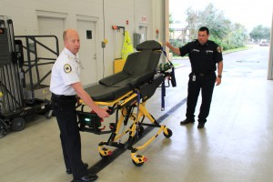 Deputy Chief Harold Theus and firefighter Justin Patterson demonstrate how the wider stretcher works on Thursday morning. (Glenn Kenelly/WUFT News)