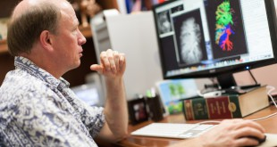 Walter O'Dell looks at a CT scan of an adult lung and its blood vessels. Comparisons can be made between traditional X-ray radiation and proton therapy to determine whether protons reduced the amount of lung damage.  Photo courtesy of UF Health