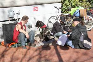 Community volunteer Greg Undeen sits with two men and their dog next to the Hippodrome downtown. Undeen works at the Helping Hands Free Medical Clinic.