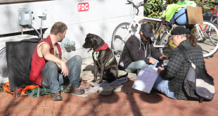 Community volunteer Greg Undeen sits with two men and their dog next to the Hippodrome downtown. Undeen works at the Helping Hands Free Medical Clinic. (Ty Schildts/WUFT News)
