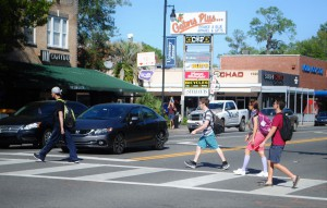 Pedestrians cross the street at the intersection of University Avenue and Fletcher Drive in Gainesville Thursday.