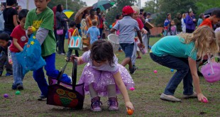 "Children reach down to pick up the colorful eggs containing candy at ""Eggolution."" Hundreds of eggs were strewn across the field, and children were divided into different age groups."
