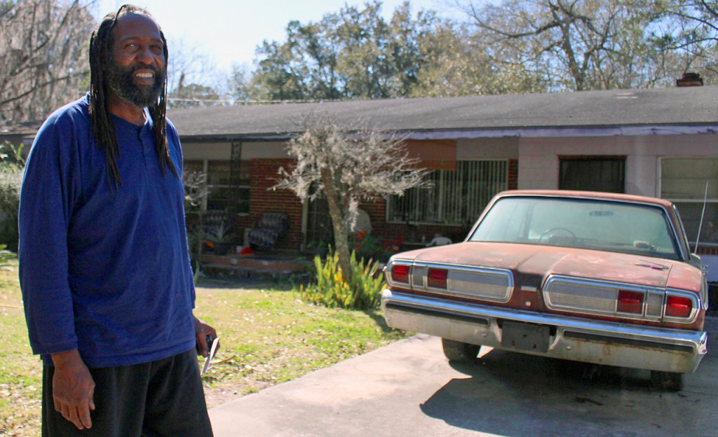 Andrew Miles stands outside the house he grew up in East Gainesville. He said he built the house next door and moved in after his mom died. He lives there with his fiance, Carla Lewis, and her son, Tyce, 14.