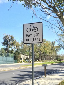 """Signs reading """"May Use Full Lane"""" with a bike image can be seen lined along NW 16th Ave. In two weeks, the road will have a dedicated bike lane instead of a shared lane for bikers and vehicles that existed previously. Photo by Kristina McDonald // WUFT News"""