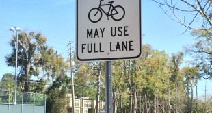 "Signs reading ""May Use Full Lane"" with a bike image can be seen lined along NW 16th Ave. In two weeks, the road will have a dedicated bike lane instead of a shared lane for bikers and vehicles that existed previously. Photo by Kristina McDonald // WUFT News"