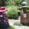 A woman sits and reflects in the glass ball in the herb garden on Sunday, April 17. (Alexandra Booth/WUFT News)