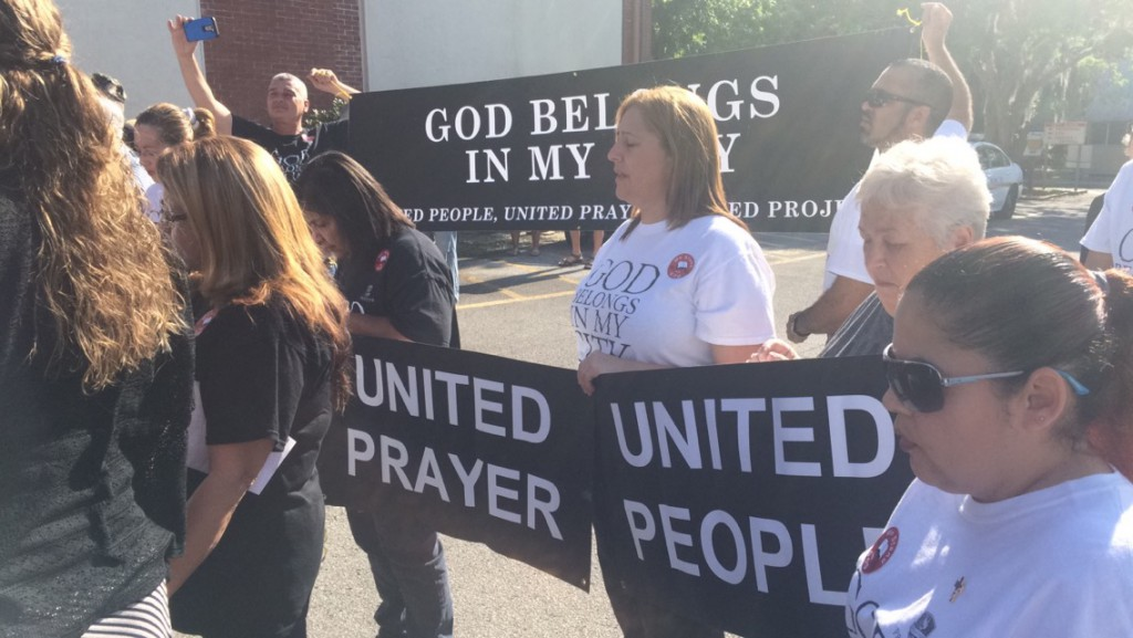 "Protesters hold signs reading ""GOD BELONGS IN MY CITY"" and ""UNITED PRAYER, UNITED PEOPLE"" outside the Marion County School Board meeting on Tuesday, April 26, 2016. (Isabella Alsina/WUFT News)"