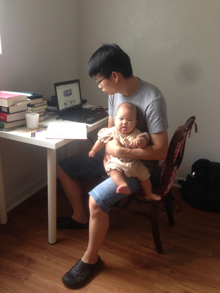 Qingming Huang held his five-month-old daughter while reading a book at the same time. He said it would take him two to three hours to watch a 40-minute-long show because he needed to take care of his daughter while watching the show. (Courtesy of Tao Lin)