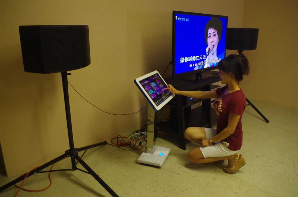 """Zhuo Jia selects songs using the Karaoke machine in her restaurant. """"Cooking and singing are two of my favorite things, and I would like to implement these two things in my restaurant,"""" Jia said. (Photo by Zhiming Zhang/WUFT News)"""