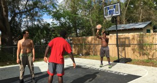 Tyree Thomas, 16, shoots a free throw on the new 24x30 foot basketball court in his backyard the Gainesville Police Department and the Basketball Cop Foundation gave him after noise complaints of Thomas and his friends being loud in the street. (Ryan Summers/WUFT News)