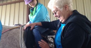 Hannah Fouche rides a horse in Ocala with the assistance of a volunteer. (Danielle Prinz/WUFT News)