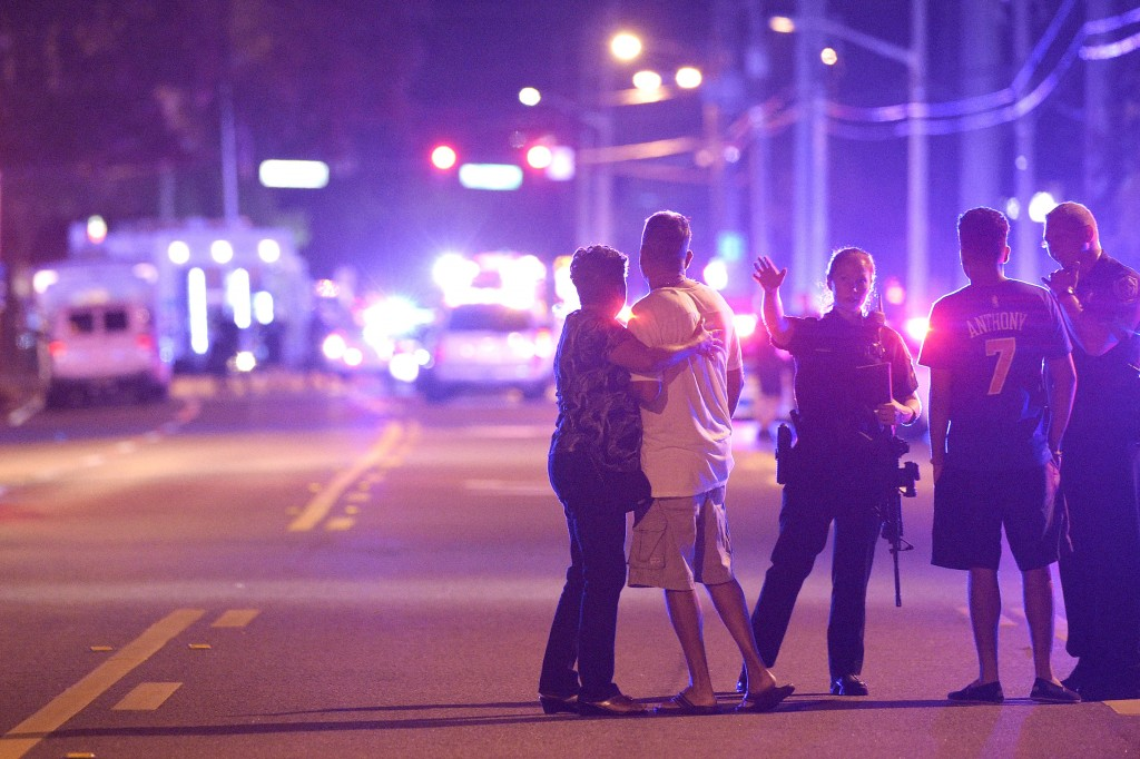Orlando Police officers direct family members away from a fatal shooting at Pulse Orlando nightclub in Orlando, Fla., Sunday, June 12, 2016. (Phelan M. Ebenhack/Associated Press)