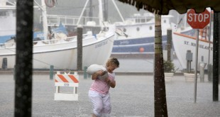 Kelly Spiliotis carries a sandbag across a flooded Athens Street on Monday, June 6, 2016, in Tarpon Springs, Fla., en route to her Ambrosia gift shop as Tropical Storm Colin barreled up the west coast of Florida. Residents on Florida's Gulf coast filled sandbags, schools closed early and graduation ceremonies were postponed as Gov. Rick Scott declared a state of emergency with Tropical Storm Colin churning toward the state Monday, threatening serious flooding. (Douglas R. Clifford/The Tampa Bay Times via AP)