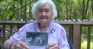 June Whitehurst, wearing her silver U.S. Marines insignia pin, talks about her service as one of the nation's first enlisted women Marines on active duty during World War II. She started working on her scrapbook in the early 1940s and has preserved handwritten letters, wartime documents and photos in its aged pages. (Brittany Valencic/WUFT News)