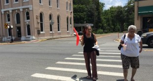 Newberry resident Angela Kogler, 52, uses a flag to attract a driver's attention as she and her mother, Helen Ellefson, 73, cross State Road 26. The flags were recently installed to improve pedestrian safety at the busy intersection. (Li Stalder/WUFT News)